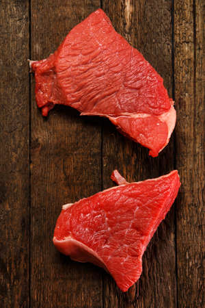 Raw meat on wooden table photo