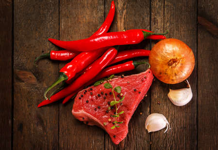 Raw meat and vegetables on wooden table photo