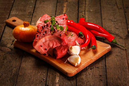 Raw meat and vegetables on wooden table