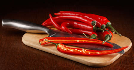Chili pepper and knife on board Stock Photo