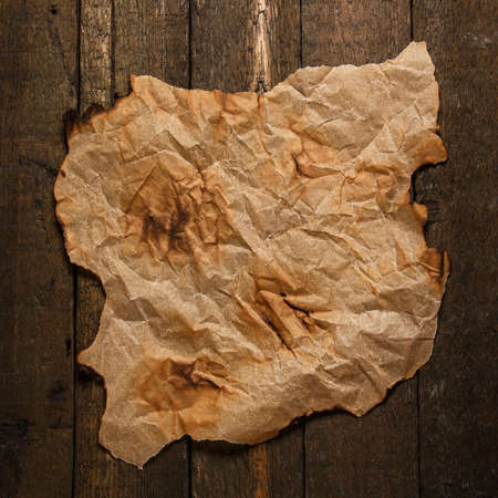 burnt paper: Old burnt paper on wooden surface Stock Photo