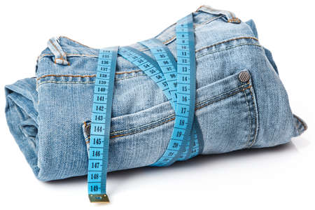 Jeans and a measuring tape on white background Stock Photo