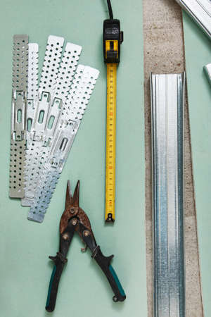 snip: Scissors for metal and measure tape on  plasterboard Stock Photo