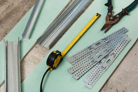 crimper: Scissors for metal and measure tape on  plasterboard Stock Photo