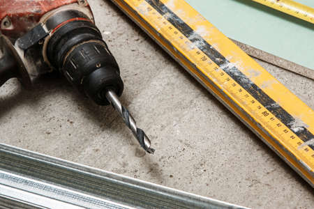 drill floor: Drill and level tool on dirty floor Stock Photo
