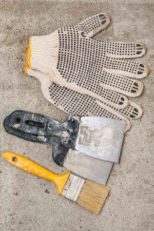 putty knives: Spatulas, brush and gloves on dirty floor