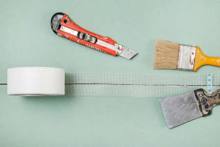 reinforcing: Reinforcing net and instruments over plasterboard surface