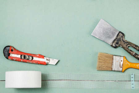putty knives: Reinforcing net and instruments over plasterboard surface