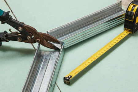 plasterboard: Scissors for metal and measure tape on  plasterboard Stock Photo