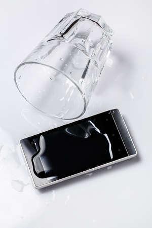 vasos de agua: Smartphone en el agua en la mesa Foto de archivo