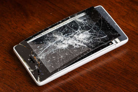 Broken smartphone with cracked display on wooden table photo