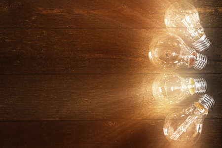 Glowing lightbulbs on wooden background photo