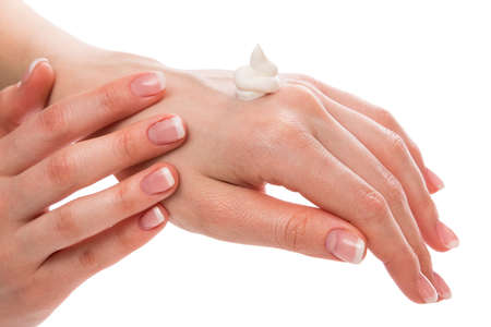 Woman applying moisturizer cream on hands with french manicure Stock Photo