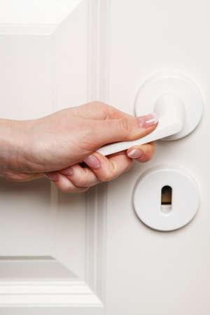 Close up of Female hand on door handle photo