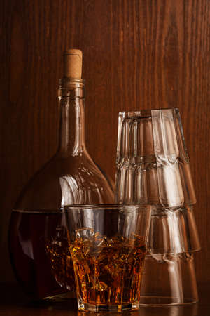 Bottle and glass with whisky on woden table photo