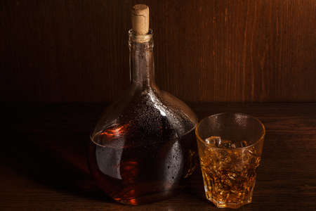 woden: Bottle and glass with whisky on woden table