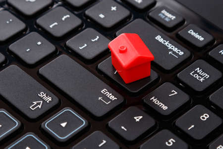 Close up of small toy house over keyboard Stock Photo