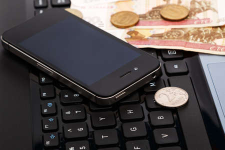 rubles: Russian rubles and smartphone over laptop keyboard