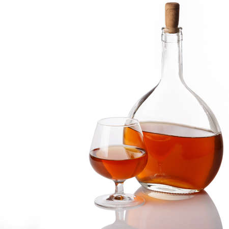 Bottle and glass with cognac on white background