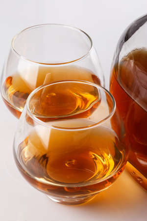 cognac: Bottle and glass with cognac on white background