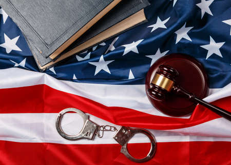auctioning: Gavel, books and handcuffs over american flag