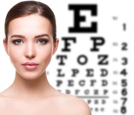 Beautiful woman and eye chart on background