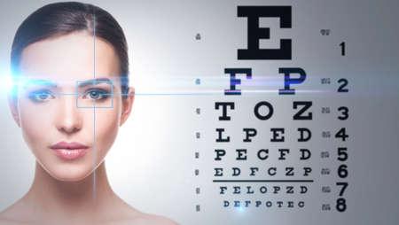 examen de la vista: Mujer hermosa y la carta de ojo en el fondo