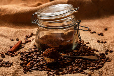 Background of roasted coffee beans and scoop with milled coffee photo
