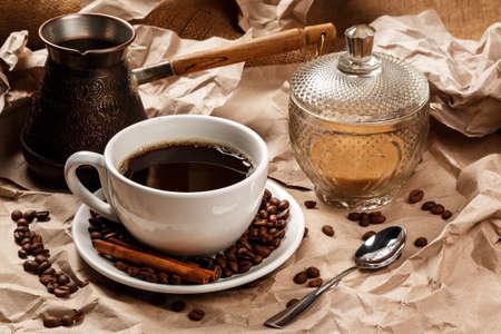 kitchen utensils: Taza de caf� y cezve para el caf� turco en la superficie de papel arrugado