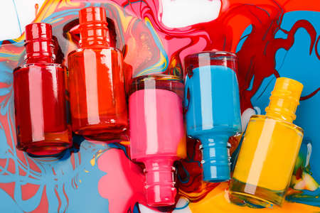 Bottles with spilled nail polish on white background