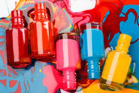 Bottles with spilled nail polish on white background