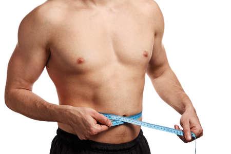 waistline: Male torso with measure tape on waistline over white background