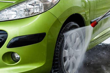 lavado: Coche verde en un túnel de lavado a mano Foto de archivo