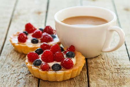 queso blanco: Taza de café y dulces pasteles con bayas en la mesa de madera