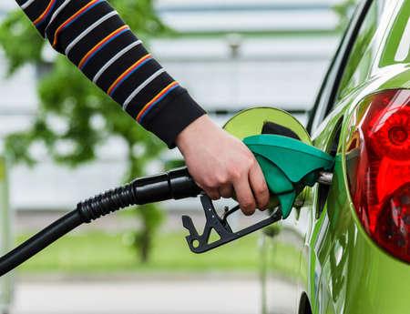 De mens vult zijn auto met een benzine bij tankstation