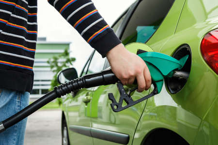 fills: Man fills up his car with a gasoline at gas station Stock Photo