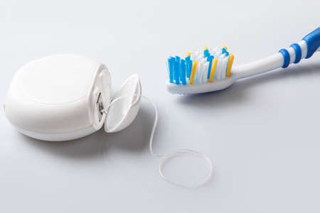caries dental: Primer plano de cepillo de dientes y seda dental