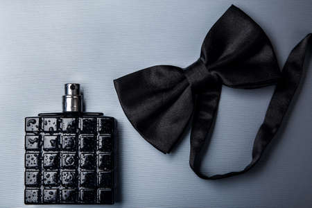 Bottle of male perfume and black bow tie Stock Photo