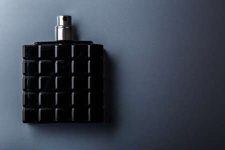 Black bottle of male perfume on metal surface 스톡 콘텐츠