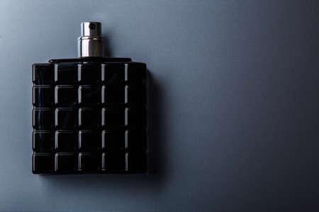 Black bottle of male perfume on metal surface Foto de archivo