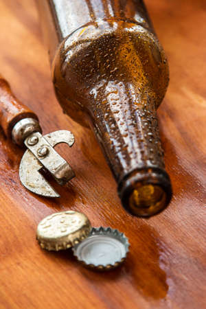 the opener: Vintage opener and beer over wooden surface