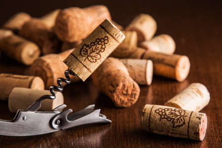 Corkscrew and corks on wooden table