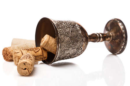grail: Old goblet and wine corks on white background