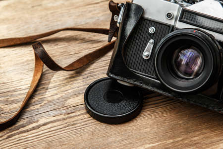 r image: Retro camera in leather case on wooden surface