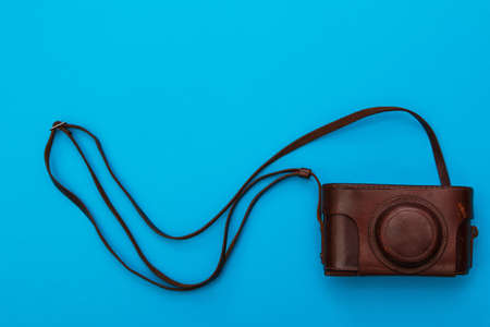camera: Retro camera in leather case on blue background Stock Photo