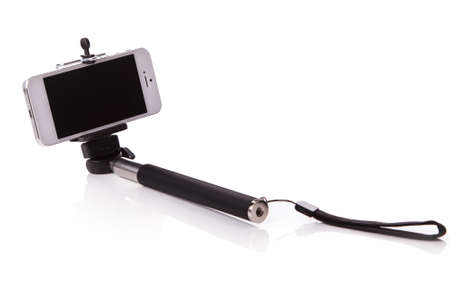 Smart phone on a selfie stick over white background Stock Photo