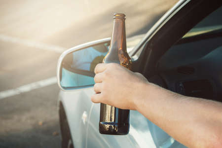 Car driver is holding a bottle of beer in his hand