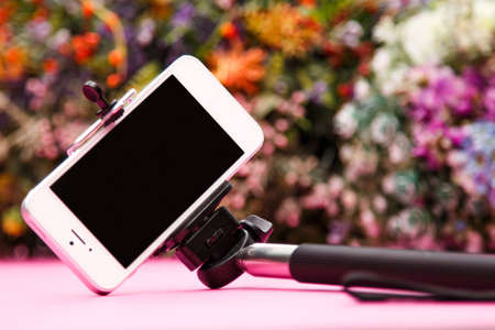 extensible: Smart phone and selfie stick on background with flowers