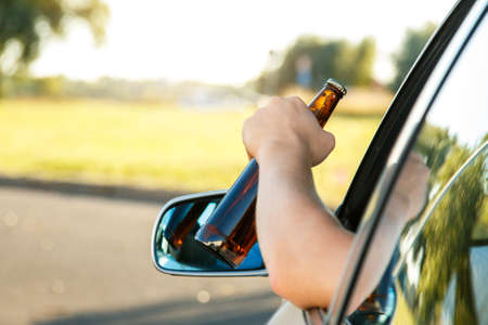 dipsomania: Car driver is holding a bottle of beer in his hand