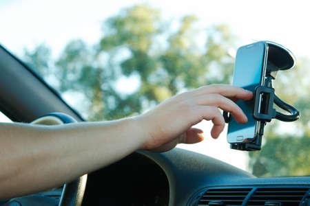 to navigation: Mano masculina y el tel�fono inteligente en un coche